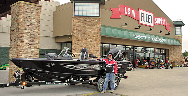 Tom Neustrom pauses for a photo with his Lund Boat outside the L&M Supply flagship store in Grand Rapids, MN during an In-Store Appearance.